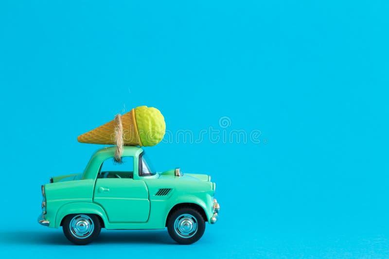 Autostuk speelgoed en roomijs tegen blauwe achtergrond op de wegsamenvatting royalty-vrije stock fotografie