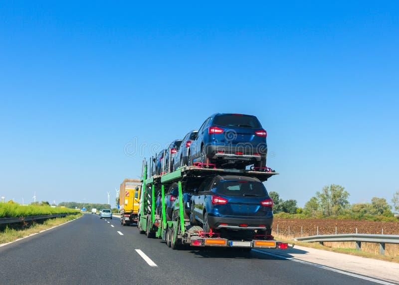 Autotransporteranhänger mit Autos auf Kojenplattform Autotransport-LKW auf der Autobahn Raum für Text lizenzfreies stockbild