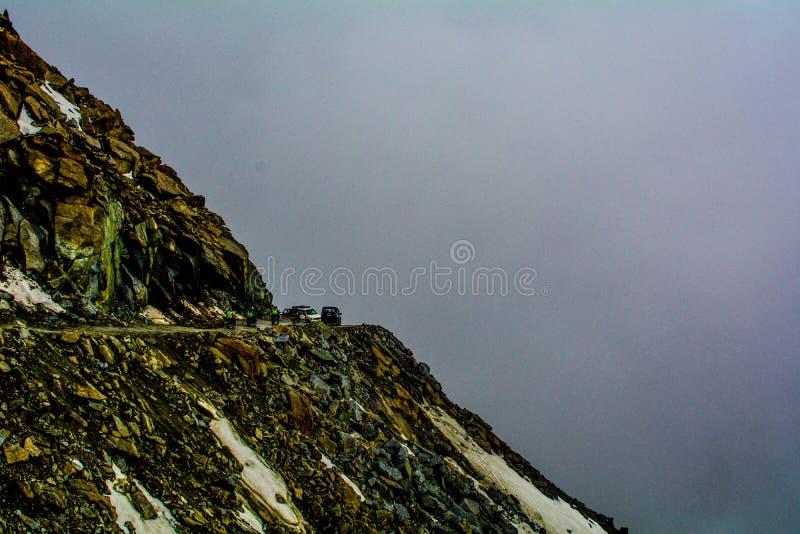 Autounfall mitten in einer curvy gefährlichen Straße auf einem hohen Felsen mit Polizeibeamten herum lizenzfreie stockfotos
