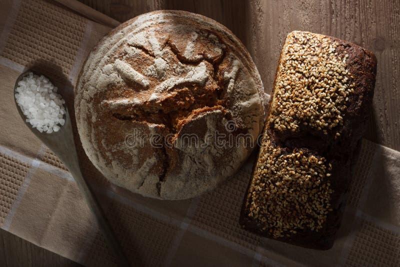 Autour de et pain carré de blé et de seigle avec une cuillère de sel dans un style rustique pendant le matin photos libres de droits
