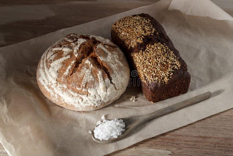 Autour de et de seigle pain noir avec le sésame et une cuillère de sel sur le papier image stock