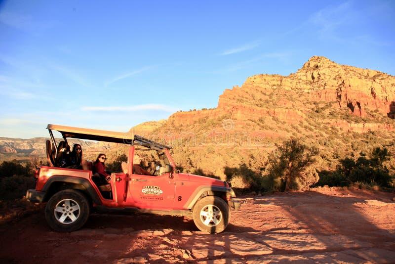Autoveicolo rosso su Brown Rock Field durante il tramonto immagini stock