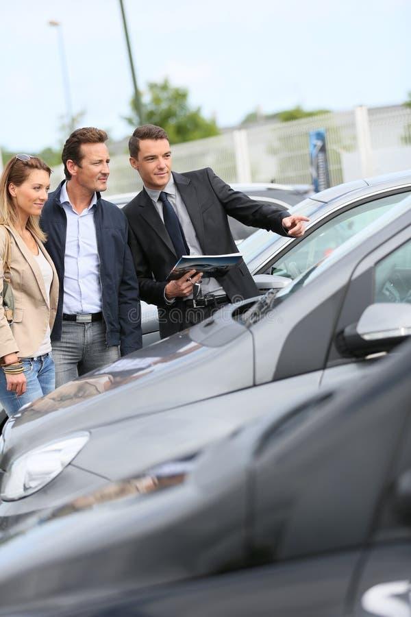 Autoverkäufer, der Autos zu den Paaren zeigt stockfotografie