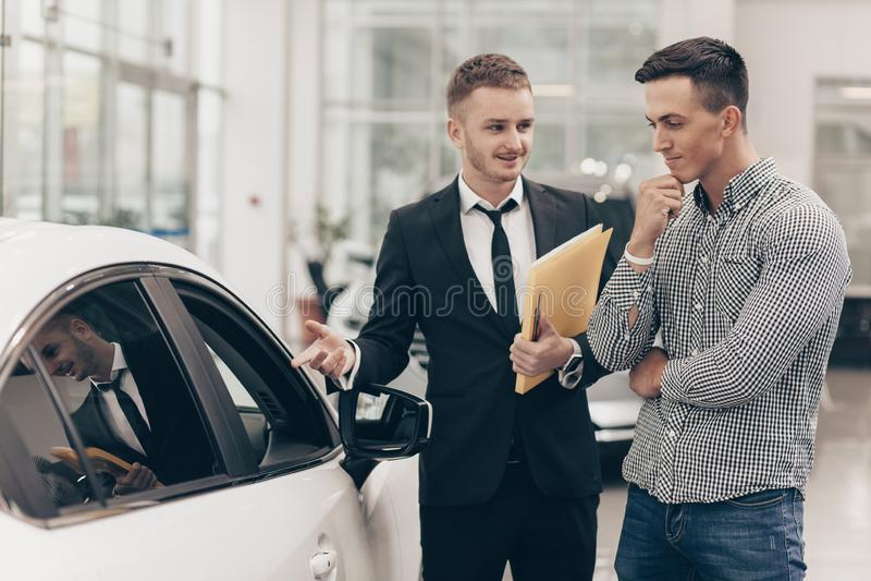 Autoverkäufer, der mit einem Kunden an der Verkaufsstelle arbeitet stockbilder