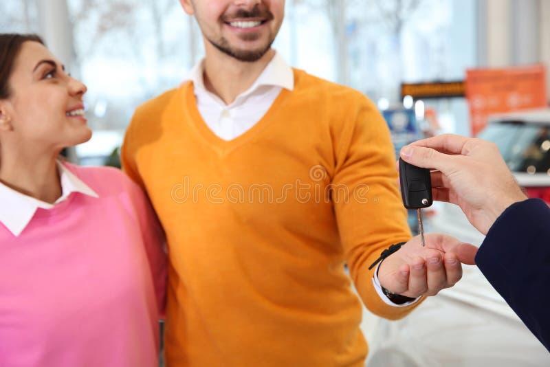 Autoverkäufer, der Schlüssel gibt, um in der Verkaufsstelle zu verbinden stockfotografie