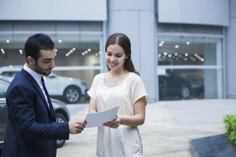 Autoverkäufer und junge Frau, die über der Schreibarbeit einem Auto-Vertragshändler betrachten stockbild