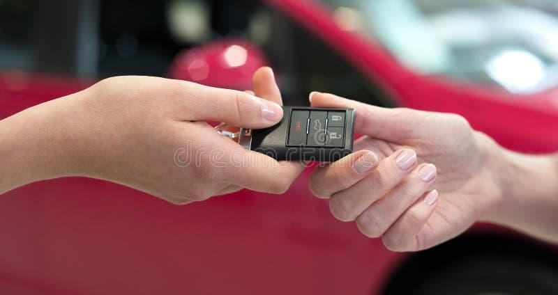 Autoverkäuferin, welche die Schlüssel für einen Neuwagen überreicht lizenzfreie stockfotografie