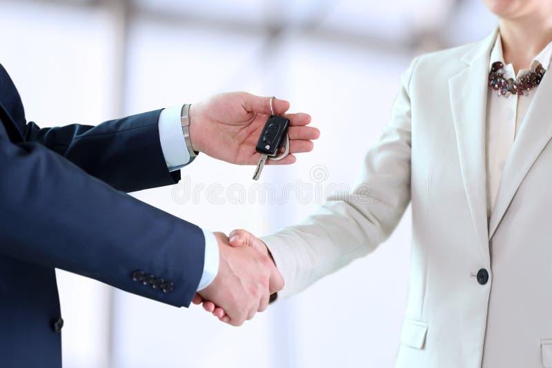 Autoverkäuferin, welche die Schlüssel für einen Neuwagen zu junge Geschäftsleute überreicht stockfotos