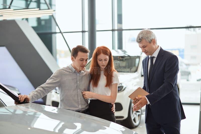 AutoVerkaufsleiter, der den Kunden über die Funktionen des Autos an der Verkaufsstelle spricht lizenzfreie stockfotografie
