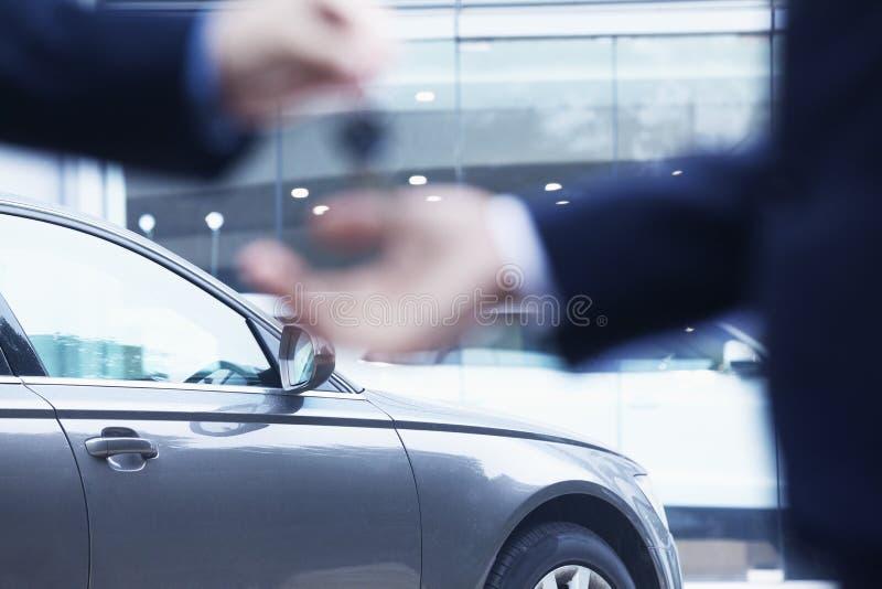 Autoverkoper die de sleutels voor een nieuwe auto overhandigen aan een jonge zakenman, close-up royalty-vrije stock foto