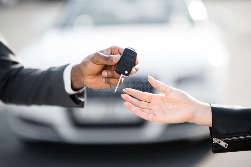 Autoverkoper het overhandigen sleutels voor nieuwe auto aan jonge vrouw stock fotografie
