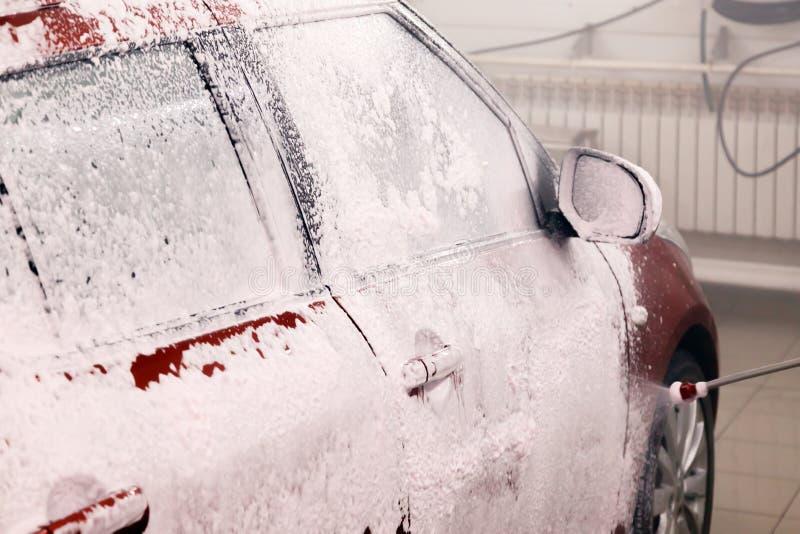 Autowasherman wendet weißen Schaum, professionelles chemisches Reinigungsmittel für Reinigungsauto auf rotem kleinem Auto an Konz lizenzfreie stockbilder