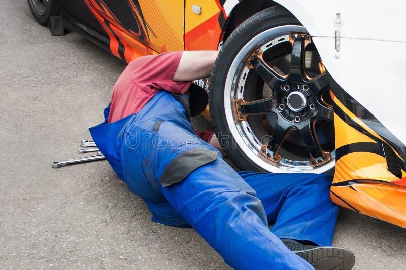Autowerktuigkundige die een auto herstellen stock afbeeldingen
