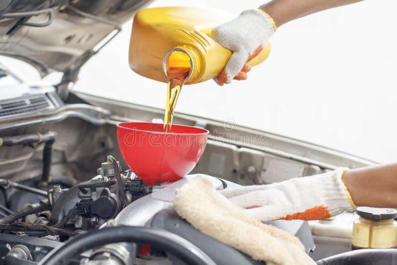 Autowerktuigkundige die nieuwe olie gieten aan motor stock afbeelding