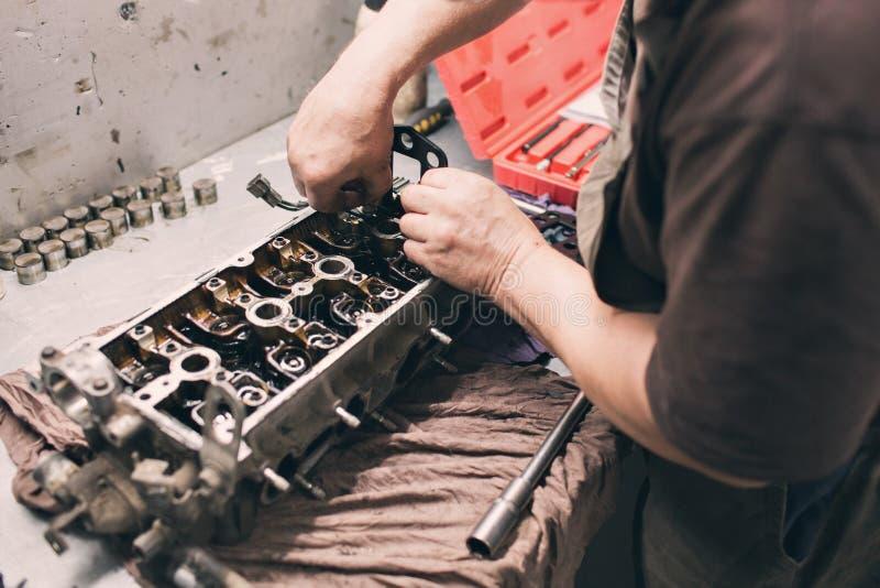 Autowerktuigkundige in garage met oude motor van een autozuiger en klep stock afbeelding