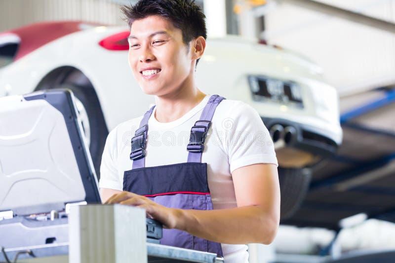 Autowerktuigkundige met diagnosehulpmiddel in Aziatische autoworkshop stock foto's