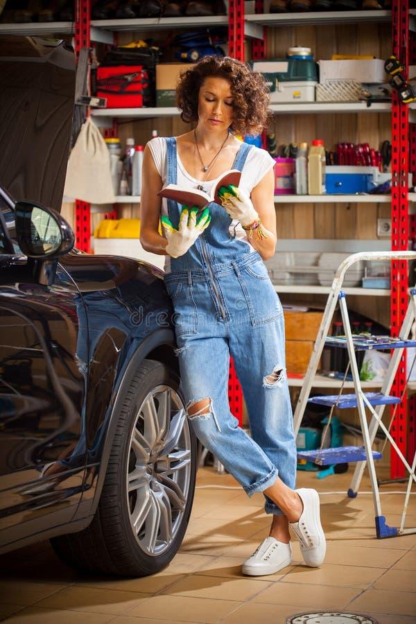 Autowerktuigkundige, vrouw die de instructies voor reparatie en aanpassing van de auto bestuderen Het voorbereidingen treffen voo royalty-vrije stock foto