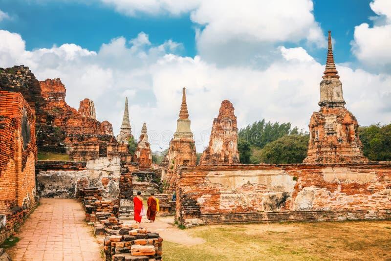 Autthaya, Tailandia - 13 de febrero de 2014: Los monjes en vestido anaranjado caminan por Wat Mahathat en complejo del templo bud foto de archivo libre de regalías
