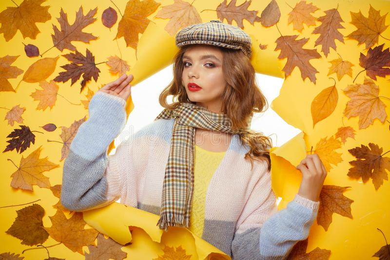 Autumn accessory trends. Pretty woman wear autumn fashion accessories. Fashion girl look through torn paper with autumn. Leaves. Fall look of vogue model stock photos