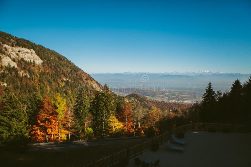 Autumn Alpine-Landschaft mit Herbstwaldbergen und -häusern unter den Felsen lizenzfreies stockfoto