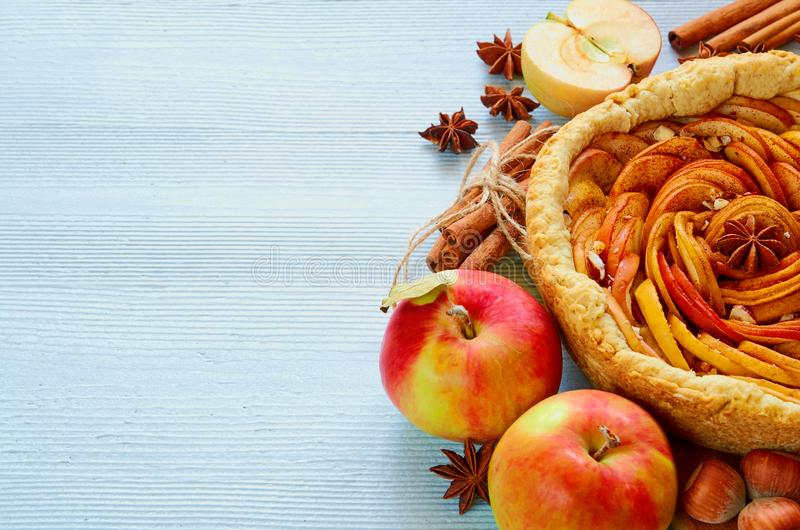 Autumn apple pie on the wooden board decorated with fresh apples, hazelnuts, spices - anise, cinnamon on the gray kitchen table stock image