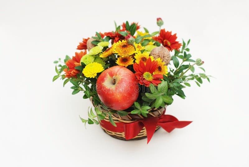 Autumn Arrangement av blommor och frukter med den röda pilbågen för gåvan som isoleras på vit bakgrund closeup royaltyfri bild