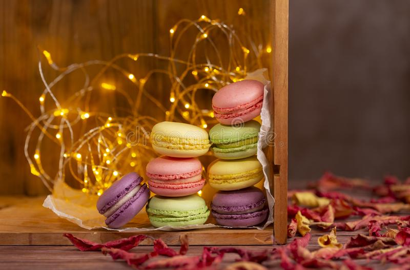 Autumn arrangement with french cookies, red dried leaves and lights with copy space royalty free stock image