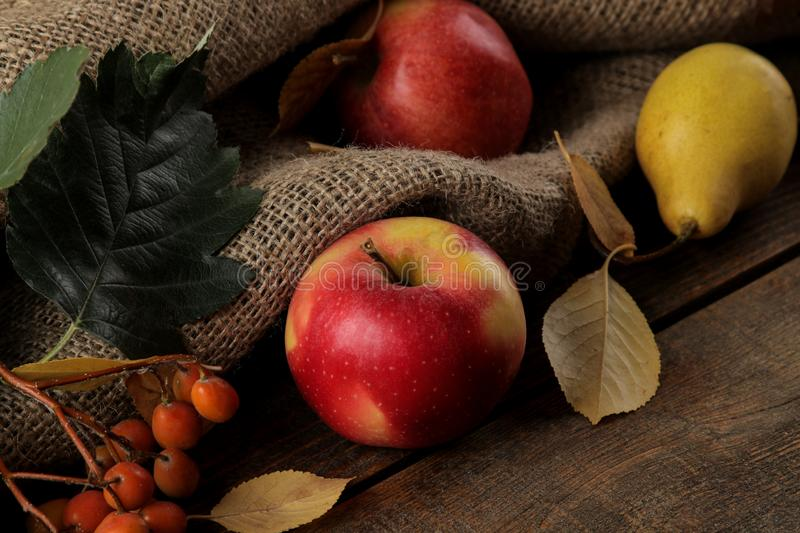 Autumn arrangement with fruit apples and pears and yellow leaves on a brown wooden table royalty free stock photo