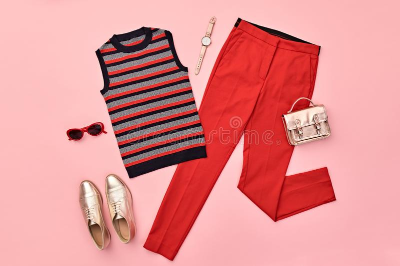 Autumn Fashion Clothes Flat lay, Leaf. Fall Outfit. Autumn Arrives. Fashion Lady Clothes fall Outfit. Trendy top, red trousers. Stylish Handbag, Gold loafers royalty free stock images