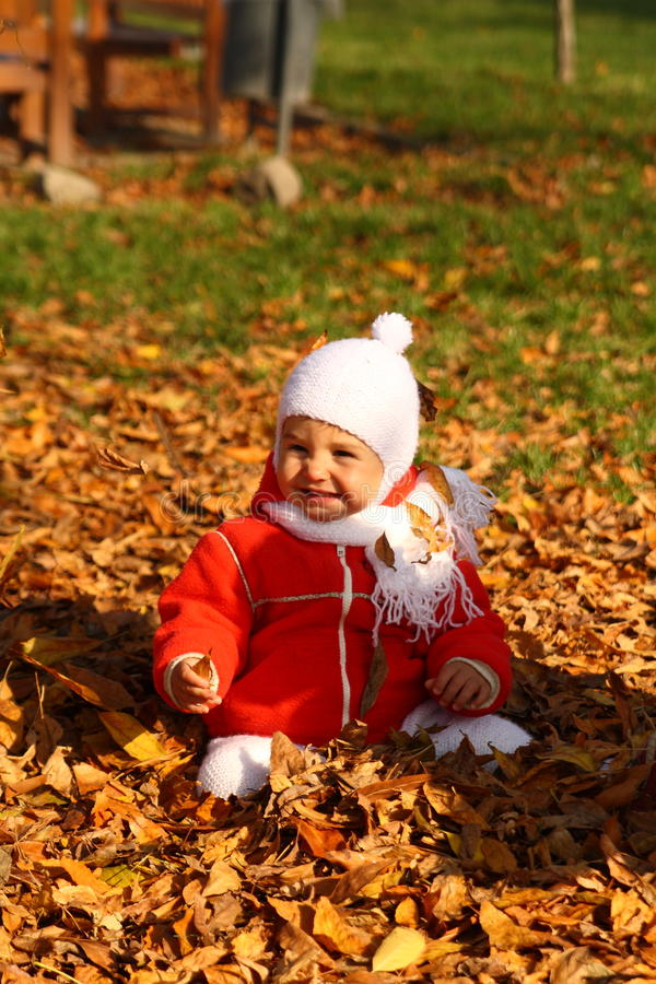Autumn baby. Baby playing with autumn leaves stock photo