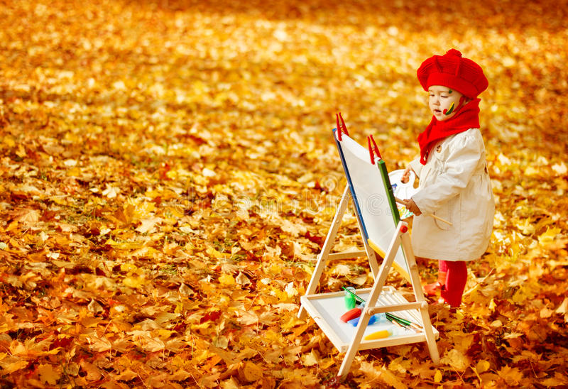 Autumn Baby Artist Painting Fall Yellow Leaves, Creative Kid stock photography
