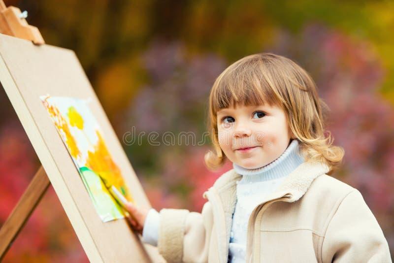 Autumn Baby Girl Drawing nella caduta lascia il parco, pittura del bambino, creatività dei bambini immagini stock