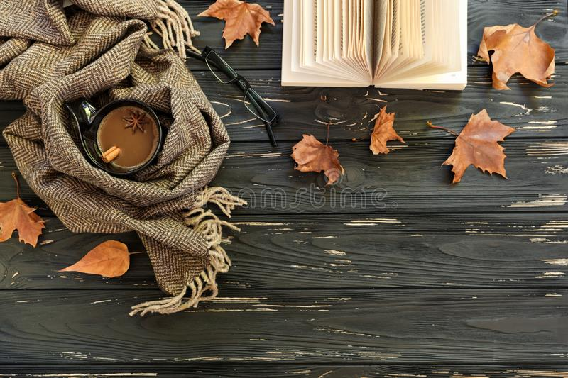 Autumn background. Cup of coffee, lambswool scarf, eyeglasses, open book, maple leaves on black wooden background, top. Aun background. Cup of coffee, lambswool stock photo