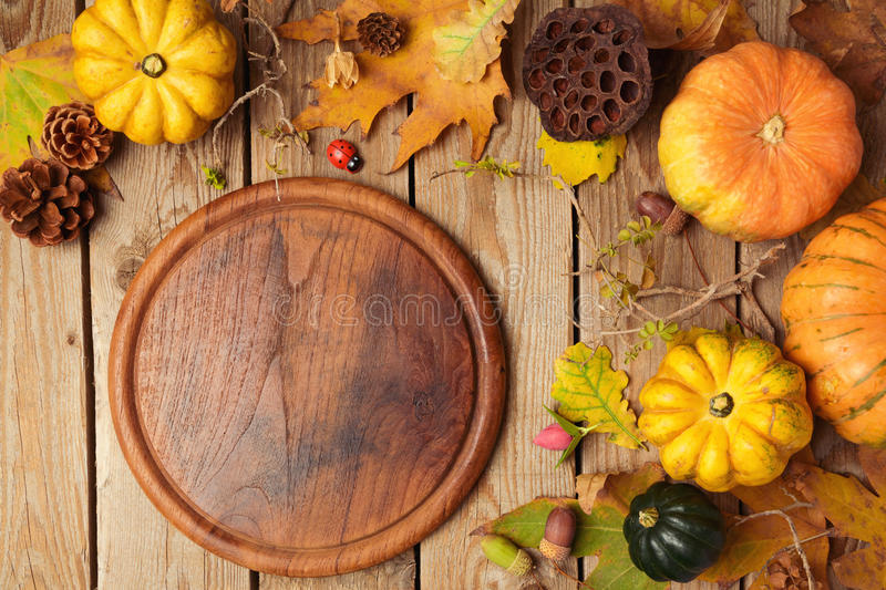 Autumn background with cutting board, fall leaves and pumpkin over wooden table. royalty free stock photography