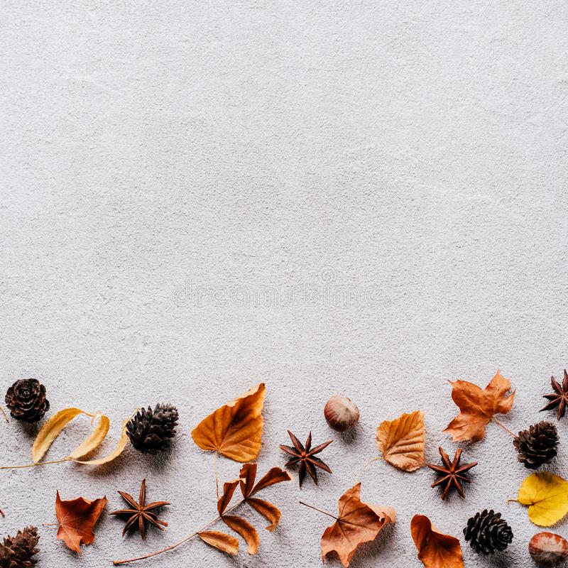 Autumn background, fall concept, thanksgiving day. Autumn vibes. Border made of dried leaves and pine cones on stone background. Seasonal background, fall stock photo