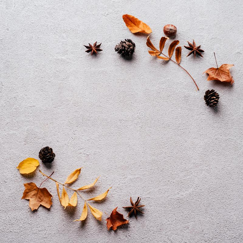 Autumn background, fall concept, thanksgiving day. Autumn vibes. Frame made of dried leaves and pine cones on stone background. Seasonal background, fall concept stock photography