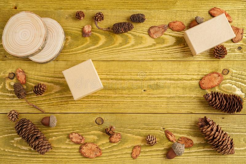 Autumn background. flat lay. wood, cones, acorns and cardboard boxes on green grunge wooden background stock images