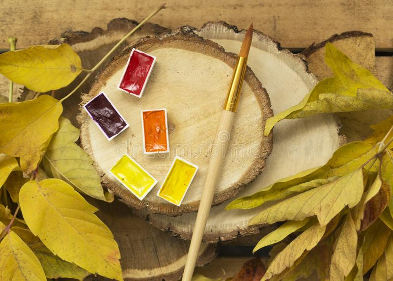 Autumn background with yellow leaves of trees, with yellow, red, orange watercolor paint and with an art brush lie on wooden log royalty free stock photos
