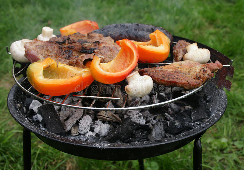 Autumn barbecue. Red peppers, mushrooms and meat on a barbecue stock photo