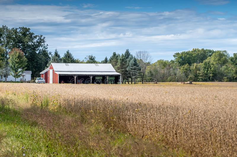 Autumn barn with golden field and farm equipment stock images