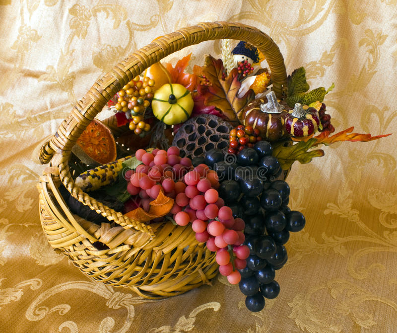 Autumn Basket. Basket with autumn decorations of grapes, gourds, greenery, berries, leaves, Indian corn on a gold table cloth stock photos