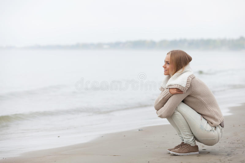 Autumn on the beach. Beautiful girl sitting on the beach royalty free stock images