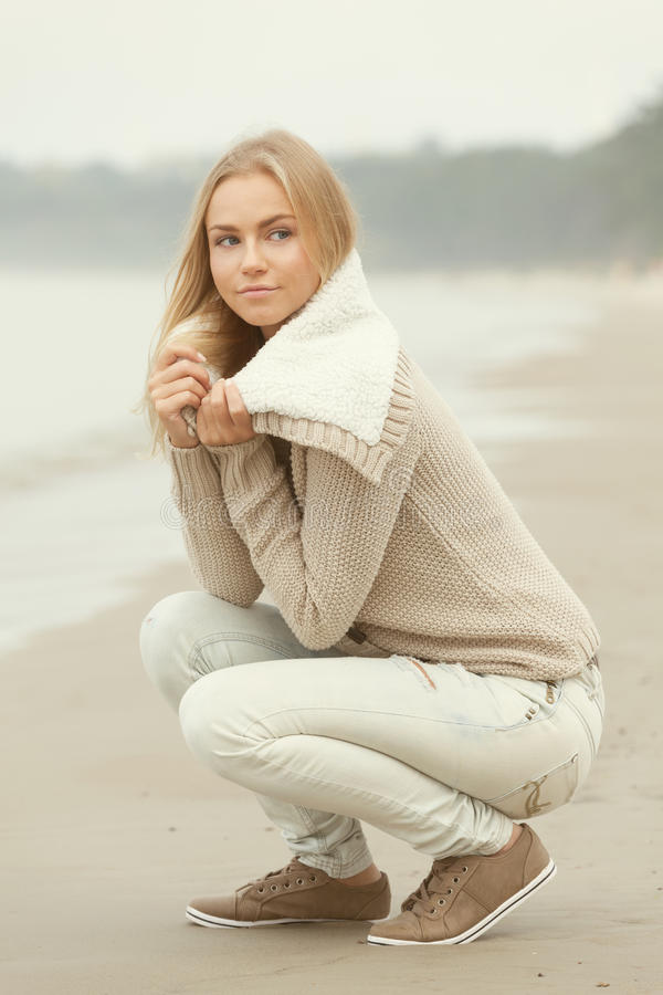 Autumn on the beach. Beautiful girl sitting on the beach royalty free stock photography
