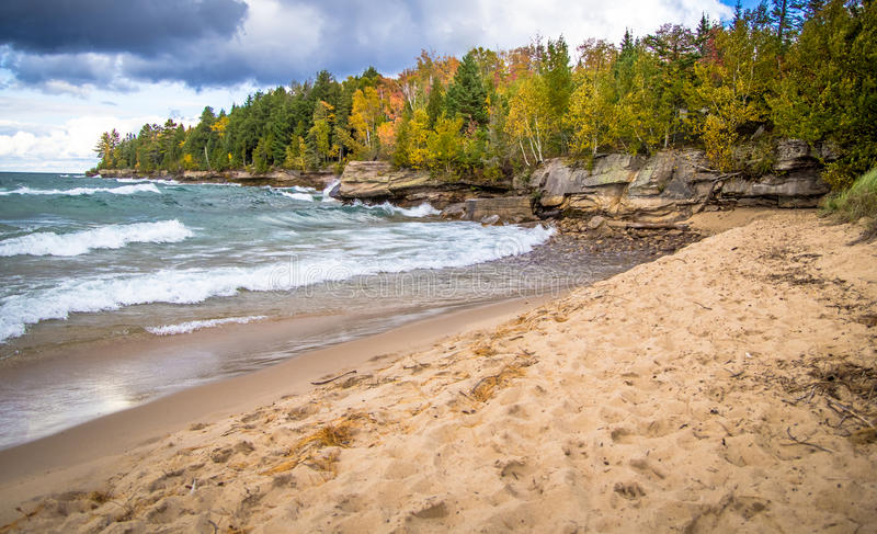 Autumn Beach On Lake Superior. Sandy beach leads to a wind swept rocky coast with the colors of autumn decorating the Lake Superior coast in Christmas, Michigan stock photography