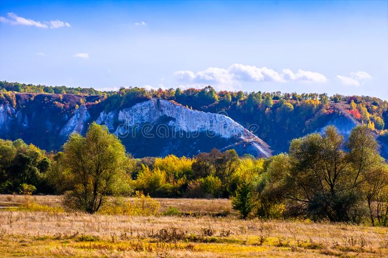 Beautiful autumn landscape. Natural chalk mountains, meadow, forest and blue sky. stock photography