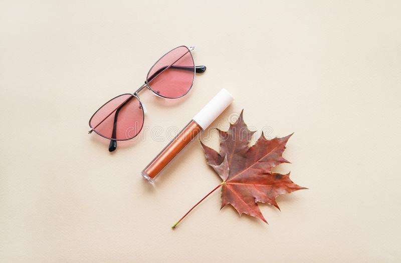Autumn beauty or fashion composition – bronze lip gloss  and pink sunglasses. Fall makeup concept. Warm colors and shades. Flat lay stock photos