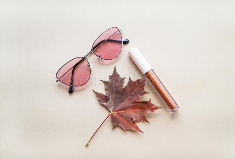Autumn beauty or fashion composition – bronze lip gloss  and pink sunglasses. Fall makeup concept. Warm colors and shades stock image