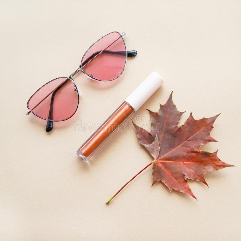 Autumn beauty or fashion composition – bronze lip gloss  and pink sunglasses. Fall makeup concept. Warm colors and shades. Flat lay royalty free stock photos