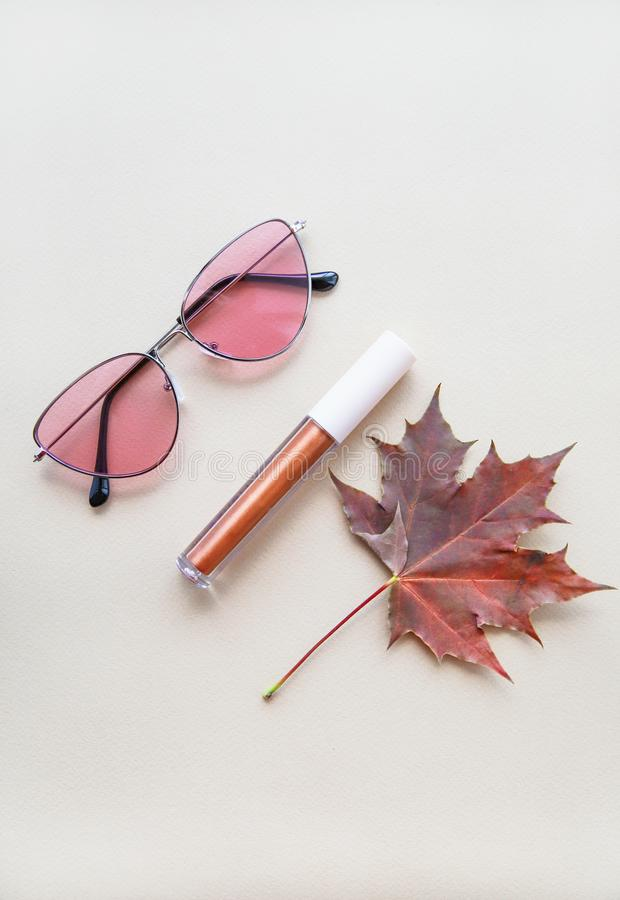 Autumn beauty or fashion composition – bronze lip gloss  and pink sunglasses. Fall makeup concept. Autumn beauty or fashion composition – bronze stock images