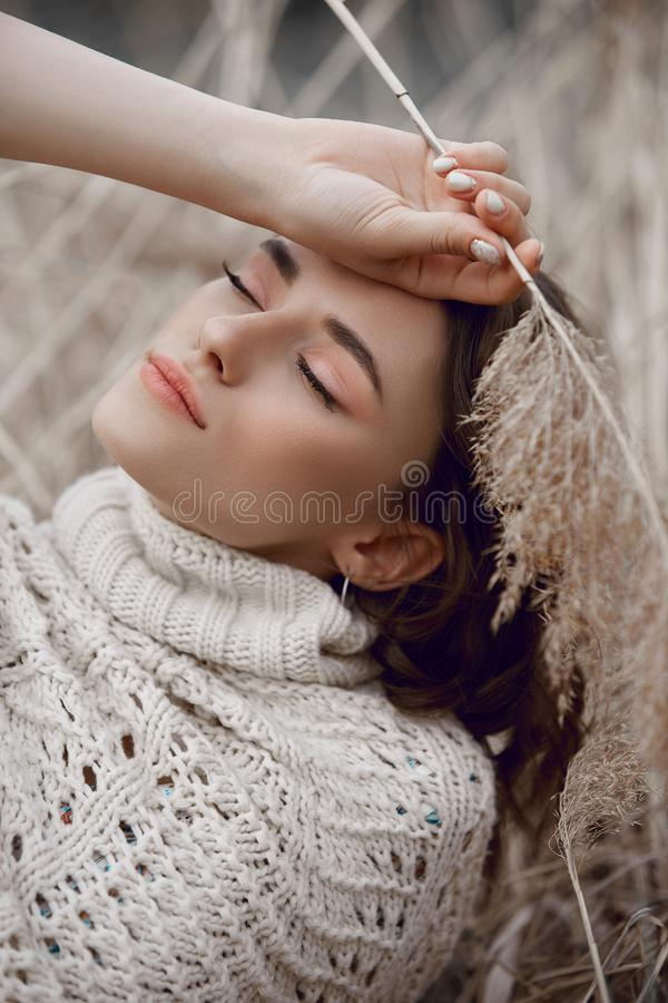 Autumn beauty portrait of a beautiful girl in a field in the grass rays of the sunset. Lifestyle woman with natural makeup on royalty free stock photography
